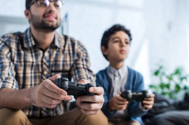 KYIV, UKRAINE - OCTOBER 15, 2019: selective focus of smiling jewish father and son playing video game stock vector