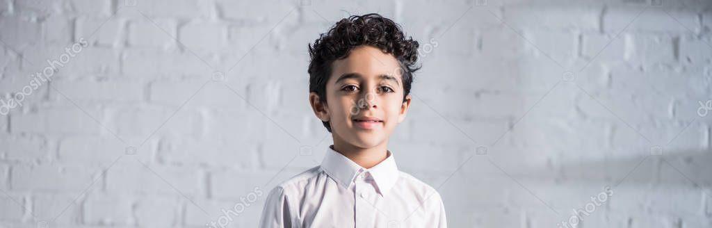 Panoramic shot of cute and smiling jewish boy in shirt looking at camera stock vector