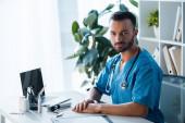 pohledný vousatý lékař při pohledu na kameru v blízkosti notebooku na klinice
