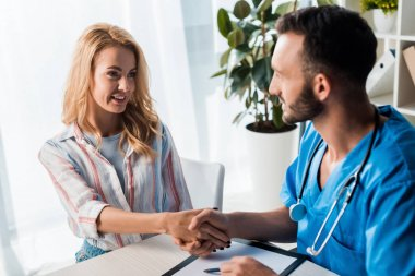 Selective focus of happy woman shaking hands with handsome doctor in clinic stock vector