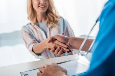 Cropped view of happy woman shaking hands with doctor in clinic stock vector