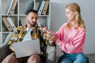 caring woman putting bandage on injured hand of bearded man sitting with laptop