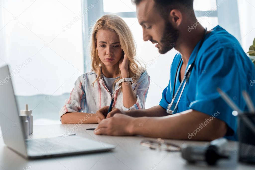 Selective focus of sad woman near doctor writing prescription stock vector