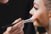 cropped view of Makeup Artist doing makeup to attractive model on backstage