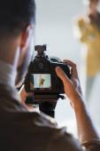 selektivní zaměření fotografování modelu s digitálním fotoaparátem v zákulisí