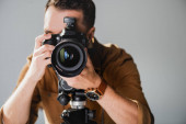 selective focus of photographer taking photo with digital camera on backstage