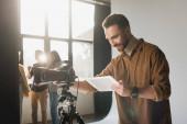Selektive Fokussierung lächelnder Fotografen mit digitalem Tablet hinter der Bühne