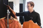 mosolygós stylist kiválasztása ruhák fotózásra a színfalak mögött