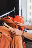 oříznutý pohled stylistky vybírající oblečení pro focení v zákulisí