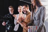 Lächelnder Fotograf, Model, Stylist und Produzent beim Anblick der Digitalkamera hinter der Bühne