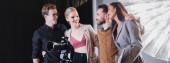 Panoramaaufnahme eines lächelnden Fotografen, Models, Stylisten und Produzenten, der sich backstage umarmt