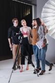 Fotografie Lächelnder Fotograf, Model, Stylist und Produzent umarmen sich backstage