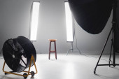 digital camera, fan, reflector, wooden stool and lights on backstage in photo studio