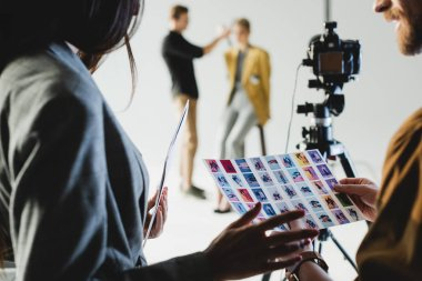 Selective focus of producer with photographer looking at references on backstage and hairstylist doing hairstyle to model on background stock vector