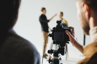 Selective focus of producer and photographer taking photo of model and hairstylist on backstage stock vector