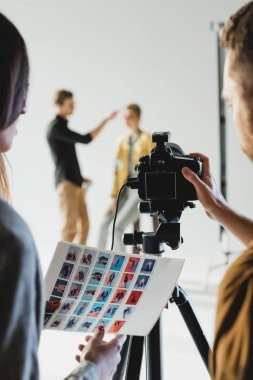 Selective focus of producer and photographer holding references and taking photo of model and hairstylist on backstage stock vector