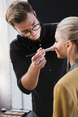 Selective focus of Makeup Artist doing makeup to model on backstage stock vector