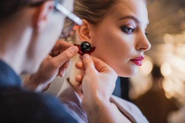 cropped view of stylist putting earring on model on backstage