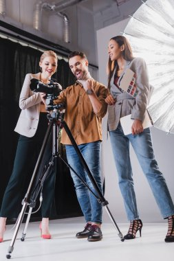 Low angle view of smiling photographer, model and producer looking at digital camera on backstage stock vector
