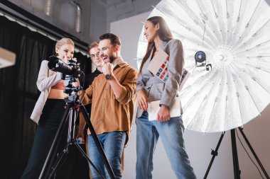 Low angle view of smiling photographer, model, stylist and producer looking at digital camera on backstage stock vector