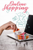 cropped view of woman holding toy shopping cart near laptop near online shopping letters on white, e-commerce concept