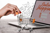 cropped view of woman holding toy shopping cart near laptop with illustration on white, e-commerce concept