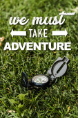 selective focus of black vintage compass on green grass near we must take adventure letters