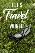 selective focus of black vintage compass on green grass near lets travel the world letters