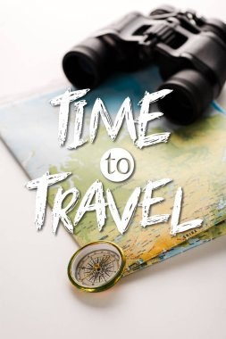golden compass near map, binoculars and time to travel letters on white