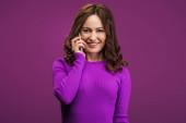 hezká, usmívající se žena mluví na smartphonu na fialovém pozadí