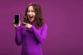 smějící se žena ukazuje prstem na smartphone s prázdnou obrazovkou na fialovém pozadí