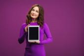 usmívající se žena drží digitální tablet s prázdnou obrazovkou na fialovém pozadí
