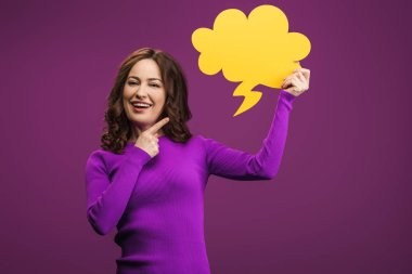 Cheerful woman pointing with finger at thought bubble on purple background stock vector