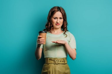 displeased woman showing refusal gesture while holding coffee to go on blue background