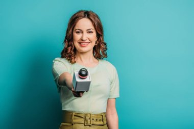 positive journalist smiling at camera while holding microphone on blue background