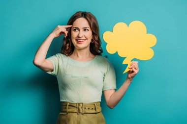 Cheerful woman showing idea sign while holding thought bubble on blue background stock vector
