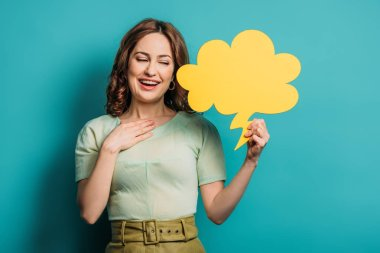 Smiling woman holding hand on chest while holding thought bubble on blue background stock vector