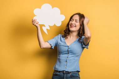 Excited girl laughing while holding thought bubble on yellow background stock vector