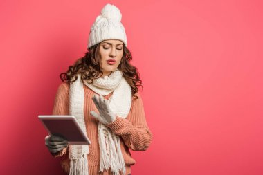 displeased girl in warm hat and scarf holding digital tablet and showing stop gesture on pink background