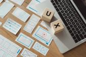 Hochwinkelansicht von Würfeln mit UX-Buchstaben auf Laptop mit Webseiten-Wireframe-Skizzen auf Holztisch