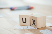 Selective focus of wooden cubes with ux letters and web sketches on table