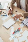 Fotografie Ausgeschnittene Ansicht eines Designers bei der Entwicklung von App-Layouts neben mobilen Wireframe-Skizzen auf dem Tisch
