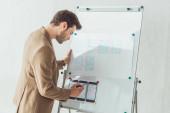 Boční pohled kreativního designéra, který si dělá poznámky o aplikačním rozhraní na tabuli v kanceláři
