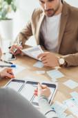 Selektivní zaměření kreativních designérů plánování náčrtků pro mobilní webové stránky u stolu