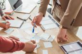 Oříznutý pohled designérů vyvíjejících uživatelský design s náčrtky na stole