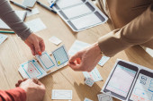 Oříznutý pohled tvůrčích designérů plánujících mobilní aplikační rozhraní u stolu