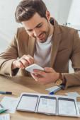 Selektivní zaměření úsměvného designéra pomocí smartphonu vedle náčrtků mobilních webových stránek na stole