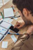 Selektivní zaměření kreativního designéra pomocí chytrého telefonu pomocí webových skic a rozložení na stole