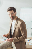 Handsome designer looking at camera while holding sketches by table