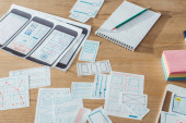 Selective focus of mobile website sketches and layouts on wooden table